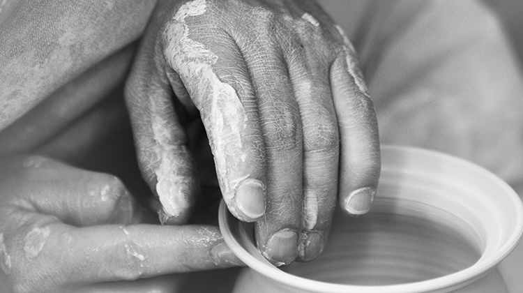 Hands working clay into pottery