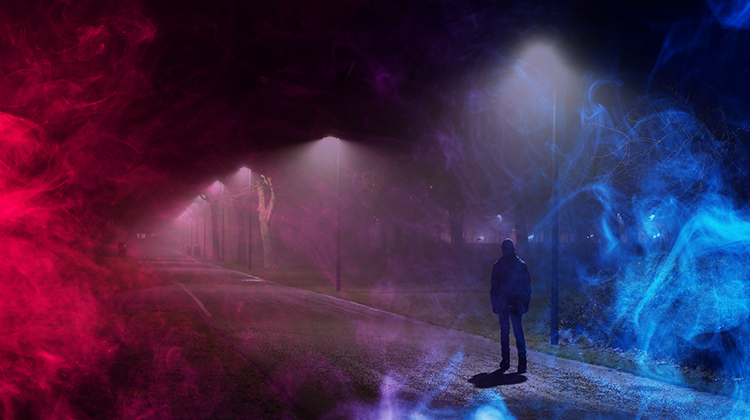 Man walking down dark path with colorful fog