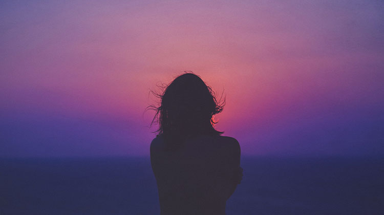 Silhouette of woman watching a sunset